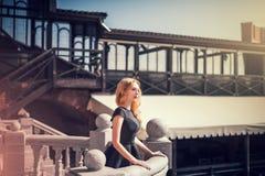 Schöne junge blonde Frau in einem schwarzen Kleid Stockfotos