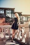 Schöne junge blonde Frau in einem schwarzen Kleid Stockfotografie