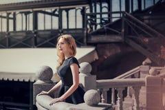 Schöne junge blonde Frau in einem schwarzen Kleid Lizenzfreie Stockfotografie
