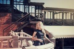Schöne junge blonde Frau in einem schwarzen Kleid Lizenzfreie Stockbilder