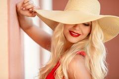 Schöne junge blonde Frau in einem Strohhut Stockbilder