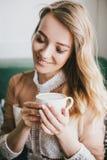Schöne junge blonde Frau in einem weißen Kleid Kaffeecappuccino mit Schaum genießend Lizenzfreies Stockfoto