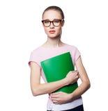 Schöne junge blonde Frau in einer Büroart, die einen Ordner hält Lokalisierung auf einem weißen Hintergrund Lizenzfreie Stockfotos