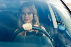 Schöne junge blonde Frau im Auto hinter dem Rad Lizenzfreie Stockbilder