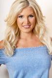 Schöne junge blonde Frau im Blau Stockfotografie