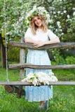 Schöne junge blonde Frau im lila Kranz auf einem Schwingen Stockfotografie