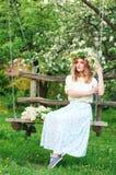 Schöne junge blonde Frau im lila Kranz auf einem Schwingen Lizenzfreies Stockfoto