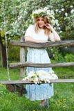 Schöne junge blonde Frau im lila Kranz auf einem Schwingen Lizenzfreie Stockfotos