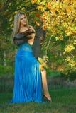 Schöne junge blonde Frau im Park mit grünen Bäumen Lizenzfreie Stockfotos