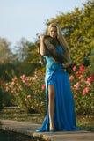 Schöne junge blonde Frau im Park mit grünen Bäumen und Blumen Stockbild