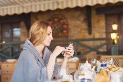 Schöne junge blonde Frau im Plaid mit Smartphone und espress Lizenzfreie Stockbilder