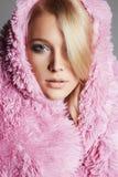 Schöne junge blonde Frau im rosa Pelz Stockfotografie