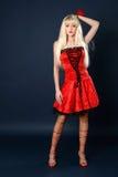 Schöne junge blonde Frau im roten Kleid Stockfotografie