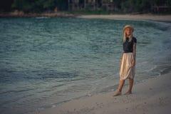 Schöne junge blonde Frau im Strohhut gehend auf den Morgenstrand auf dem Hintergrund des Türkiswassers Modernes Mädchen Lizenzfreies Stockfoto