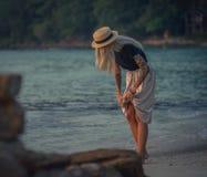 Schöne junge blonde Frau im Strohhut gehend auf den Morgenstrand auf dem Hintergrund des Türkiswassers Modernes Mädchen Stockfoto