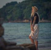 Schöne junge blonde Frau im Strohhut gehend auf den Morgenstrand auf dem Hintergrund des Türkiswassers Modernes Mädchen Lizenzfreie Stockbilder