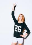 Schöne junge blonde Frau im Sweatshirt und weiße kurze Hosen hoben ihre Hand mit einem Zeichensieg an innen Warme Farbe Lizenzfreie Stockbilder