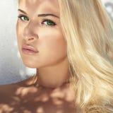 Schöne junge blonde Frau im Tageslicht Schatten auf dem Gesicht grüner Vektorhintergrund Stockfotos
