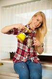 Schöne junge blonde Frau kocht Kaffee in der Küche Lizenzfreies Stockfoto