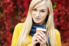Schöne junge blonde Frau mit Blättern Stockbild