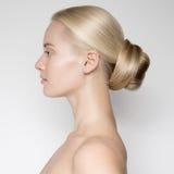 Schöne junge blonde Frau mit Brötchen Hairstуle Stockfotos