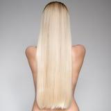 Schöne junge blonde Frau mit dem langen geraden Haar Stockbild