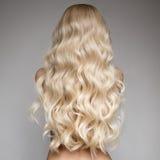 Schöne junge blonde Frau mit dem langen gewellten Haar Stockfotografie