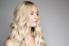 Schöne junge blonde Frau mit dem langen gewellten Haar Stockbilder