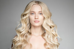Schöne junge blonde Frau mit dem langen gewellten Haar Stockbild