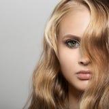 Schöne junge blonde Frau mit dem langen gewellten Haar Stockfoto