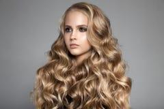 Schöne junge blonde Frau mit dem langen gewellten Haar Lizenzfreies Stockfoto