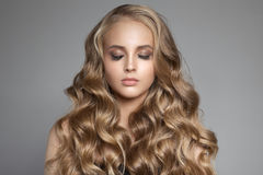 Schöne junge blonde Frau mit dem langen gewellten Haar Lizenzfreie Stockfotografie