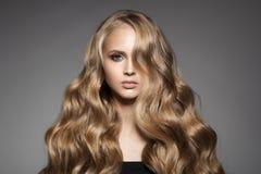 Schöne junge blonde Frau mit dem langen gewellten Haar Lizenzfreie Stockbilder