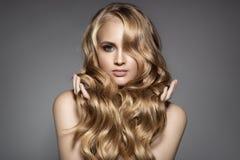 Schöne junge blonde Frau mit dem langen gewellten Haar Lizenzfreies Stockbild
