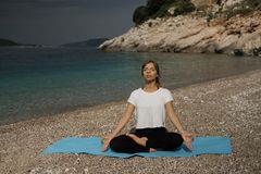 Schöne junge blonde Frau mit dem langen Haar, das Yoga und medita tut Stockfoto