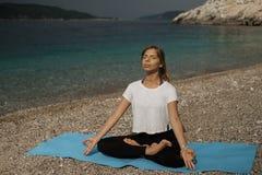Schöne junge blonde Frau mit dem langen Haar, das Yoga und medita tut Stockfotos