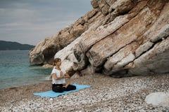 Schöne junge blonde Frau mit dem langen Haar, das Yoga und medita tut Stockfotografie