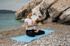 Schöne junge blonde Frau mit dem langen Haar, das Yoga und medita tut Lizenzfreies Stockbild