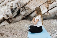 Schöne junge blonde Frau mit dem langen Haar, das Yoga und medita tut Lizenzfreies Stockfoto