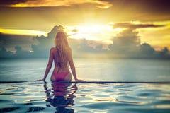 Schöne junge blonde Frau mit dem langen Haar den Sonnenuntergang f bewundernd Lizenzfreie Stockfotografie