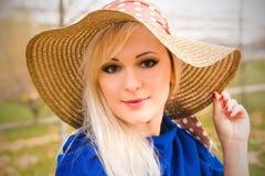 Schöne junge blonde Frau mit dem langen Haar im Hut Stockbilder