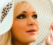 Schöne junge blonde Frau mit dem langen Haar im Hut Lizenzfreie Stockbilder
