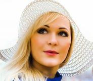 Schöne junge blonde Frau mit dem langen Haar im Hut Stockfotografie