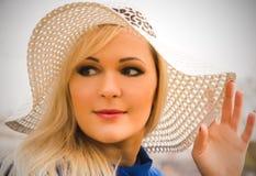 Schöne junge blonde Frau mit dem langen Haar im Hut Stockfoto
