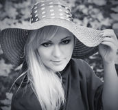 Schöne junge blonde Frau mit dem langen Haar im Hut Schwarzes und wh Stockfotografie