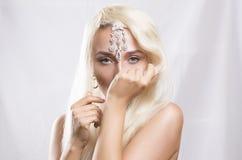 Schöne junge blonde Frau mit dem langen Haar und der Dekoration an Stockbild