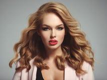 Schöne junge blonde Frau mit den sexy roten Lippen Stockfotografie