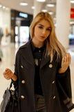 Schöne junge blonde Frau mit einem hübschen Gesicht in einem modernen modischen Mantel mit einer ledernen schwarzen Modehandtasch lizenzfreie stockfotografie
