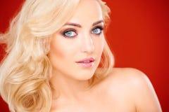 Schöne junge blonde Frau mit einem strahlenden Lächeln Lizenzfreie Stockfotos