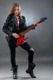 Schöne junge, blonde Frau mit einer E-Gitarre Stockfoto